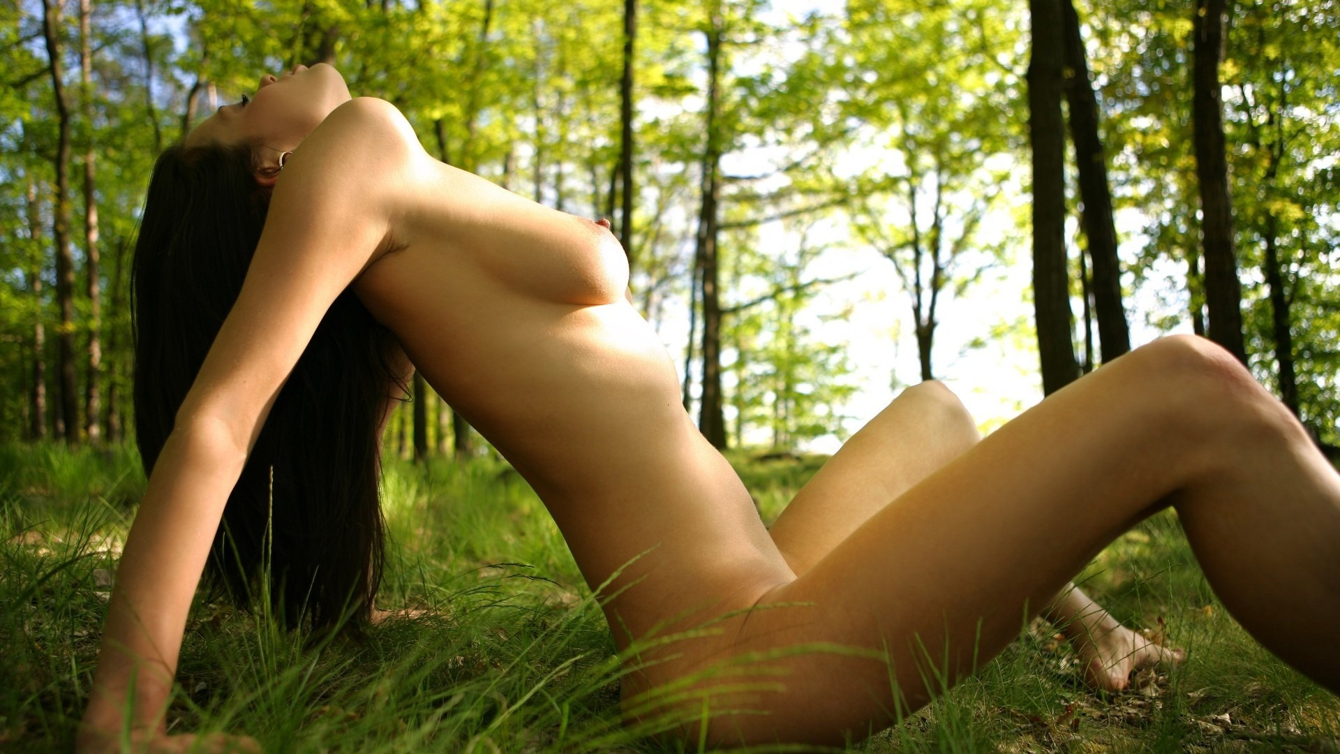 Young asian woman in natural setting naked but covered with a leaf