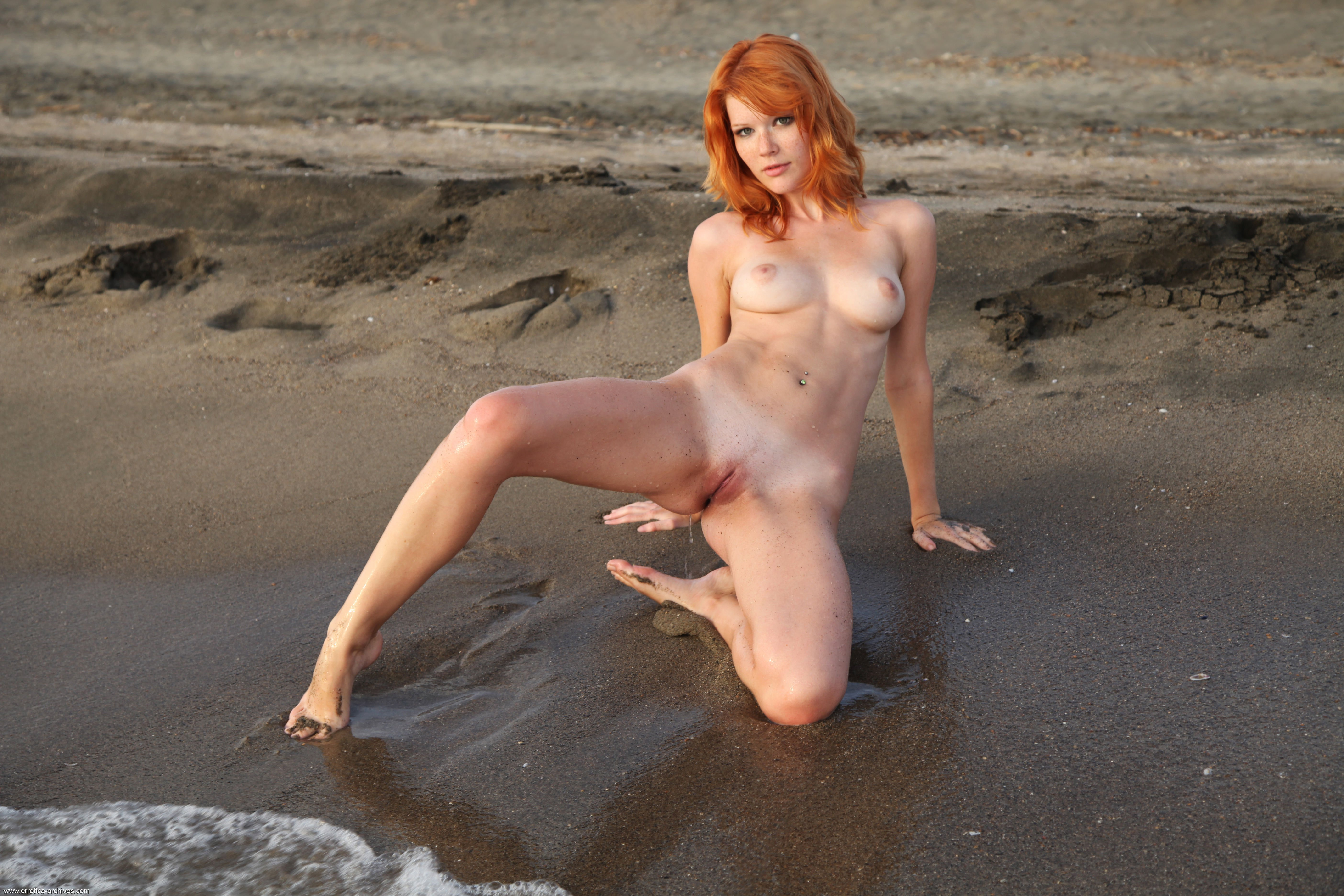 Naked feet with red nail polish in the sand on the beach
